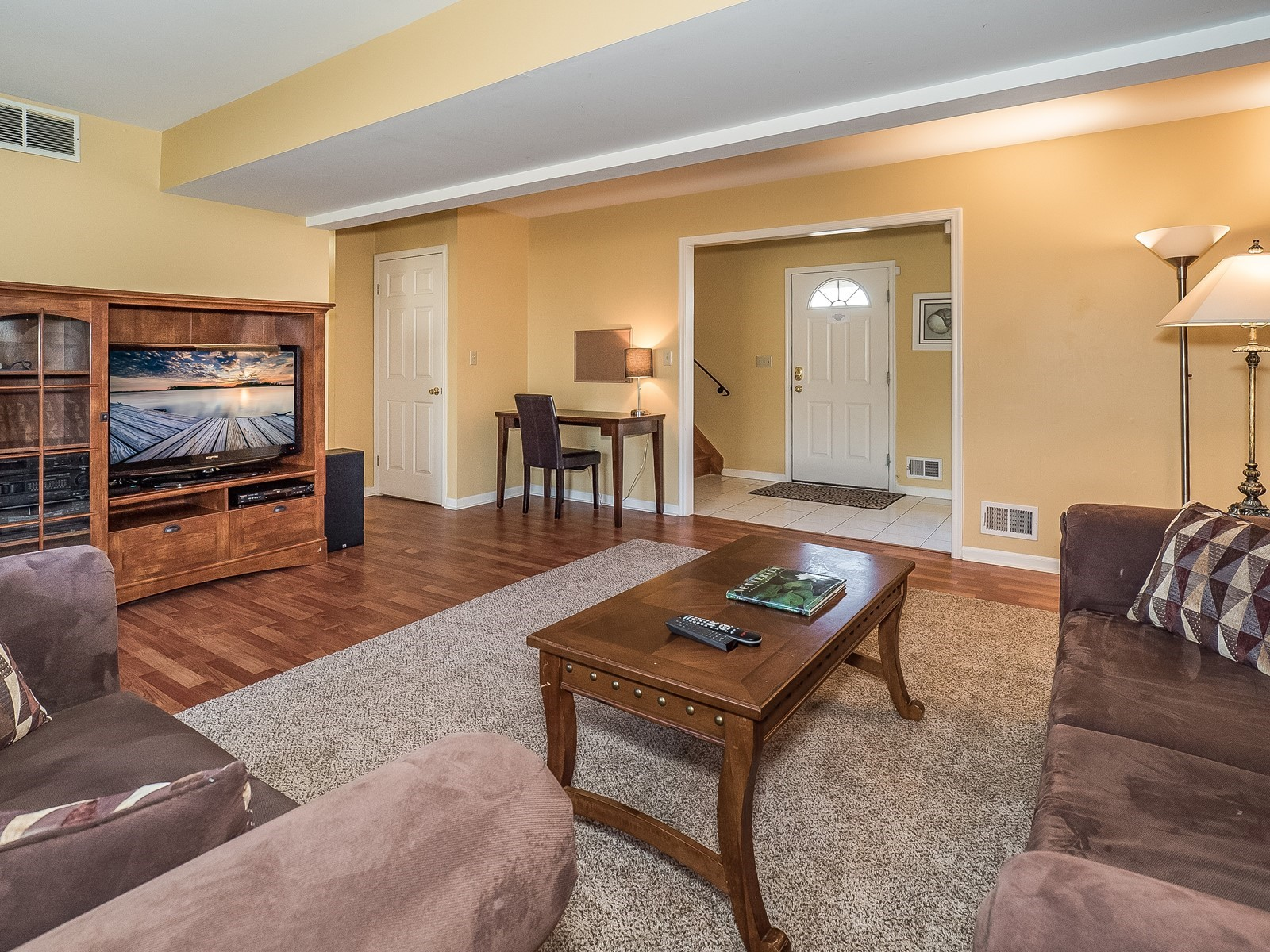Woodbridge 29 Temporary Housing downstairs living room with large tv and view into entrance