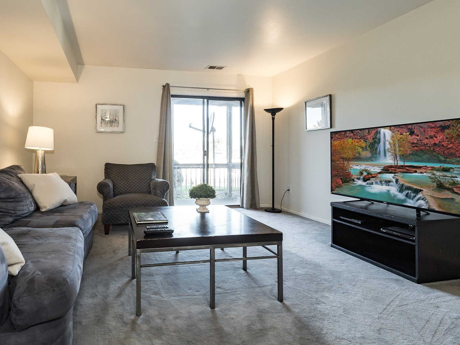 Woodbridge 404 Furnished Apartment living room with large tv and sliding glass door