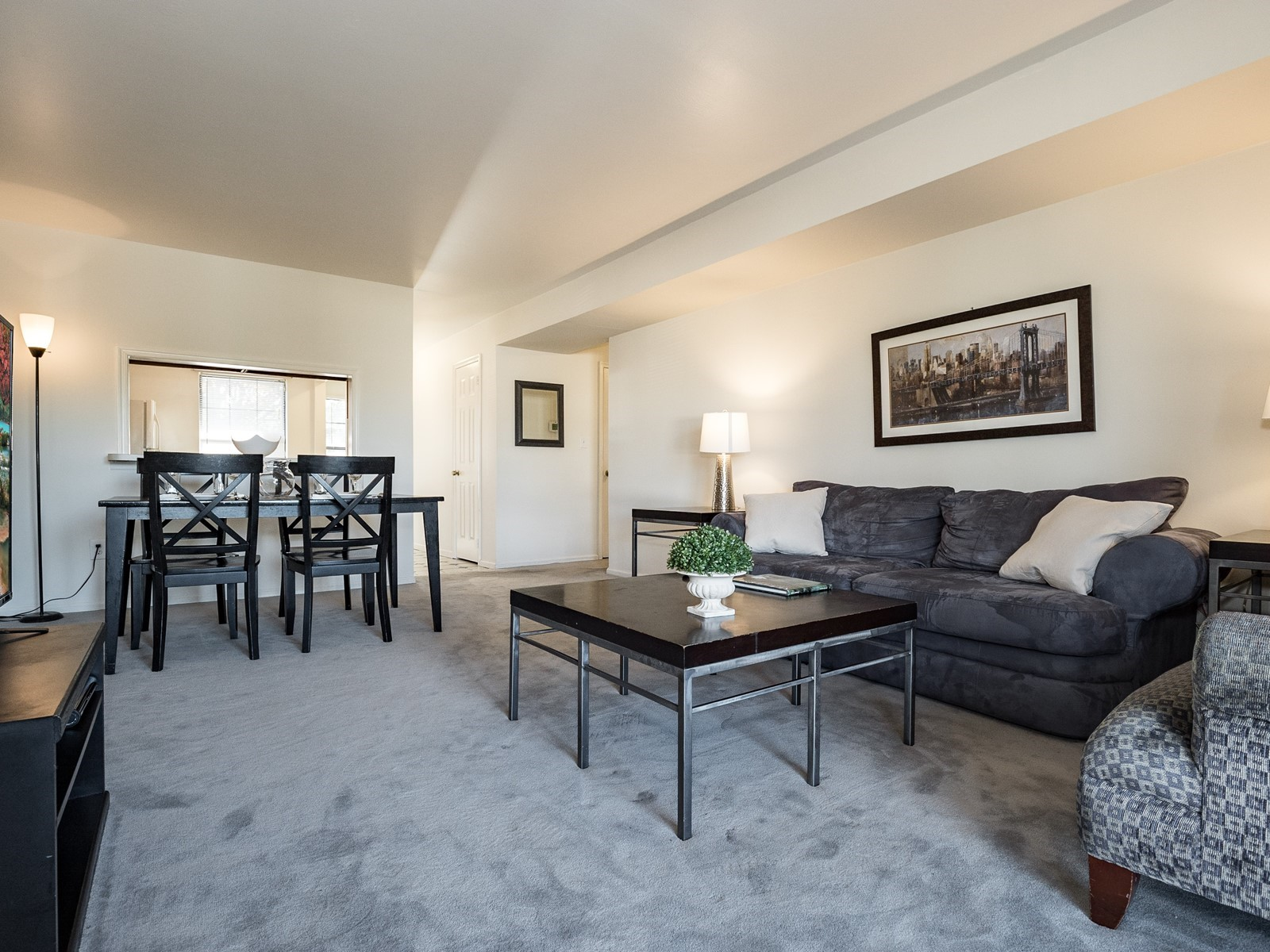 Woodbridge 404 Furnished Apartment living room with large sofa, chair and view to dining area