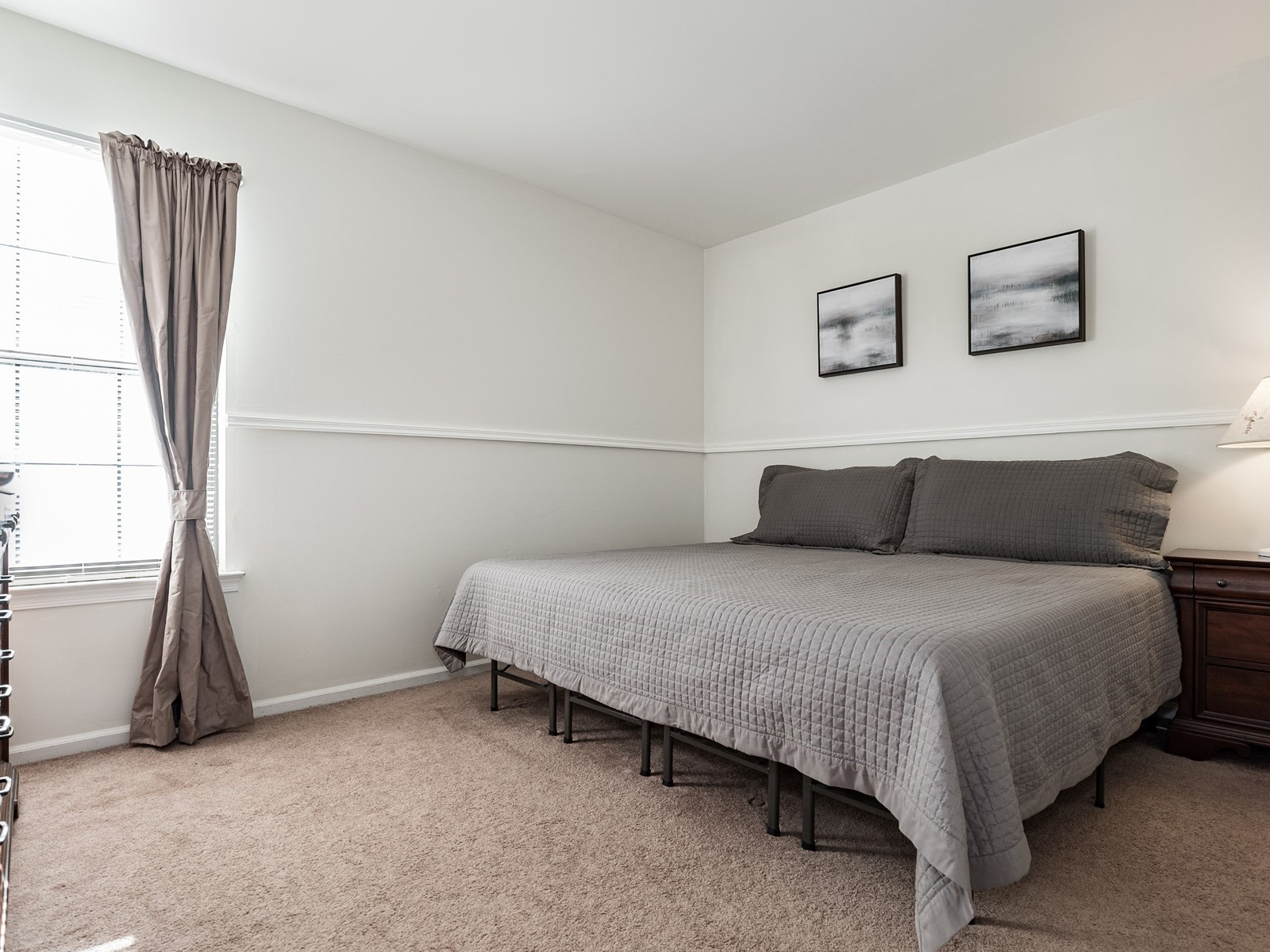 Woodbridge 404 Furnished Apartment master bedroom with king sized bed and dresser